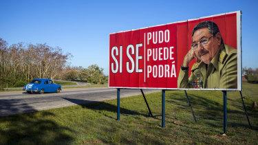 Un coche circula junto a una valla publicitaria escrita en español