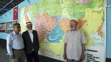 """Uighur Muslim men stand in front of map showing the area claimed by Uighur separatists as """"East Turkistan"""" marked in blue at a resettlement community in Kayseri in central Turkey."""