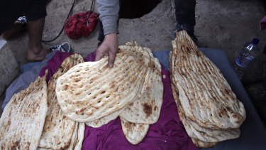 An Afghan man makes traditional bread at a makeshift camp for refugees and migrants in Lesvos.
