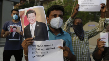 An Indian man holds a photograph of Chinese President Xi Jinping during a protest against China in Ahmedabad, India, this week.