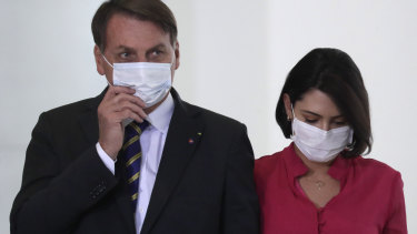 Brazil's President Jair Bolsonaro and his wife Michelle at an event in Brasilia on Wednesday, a day before she tested positive for COVID-19.