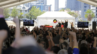 Mourners with fists upraised paid tribute to a giant of the Brisbane community.
