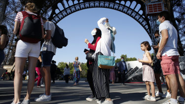 People queue up prior to visit the Eiffel Tower in Paris. The iconic landmark reopened on Thursday after its longest closure since WWII.