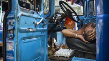 A truck driver takes a nap in the cabin of his truck at an outdoor food market in Havana, Cuba, on Saturday.
