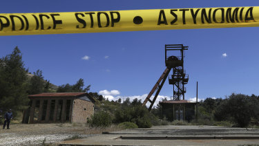 A Cypriot police office stands near the flooded mineshaft where two female bodies were found in April.