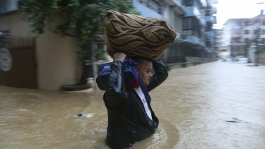 A Nepalese man wades with his belonging through a flooded street in Kathmandu, Nepal.