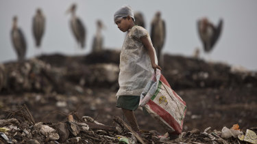 An Indian ragpicker boy searches for recyclable material  at a garbage dump on the outskirts of Gauhati, Assam state, India.