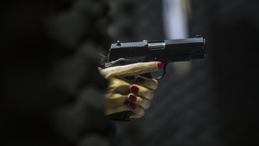 A woman holds a gun at the firing range inside the Colt 45 Shooting Club in Rio de Janeiro.
