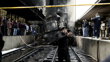 Police guard the front of a damaged train inside Ramses train station in Cairo, Egypt.
