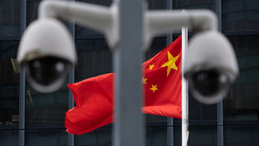 The Chinese flag flies behind a pair of surveillance cameras outside the Central Government Offices in Hong Kong.