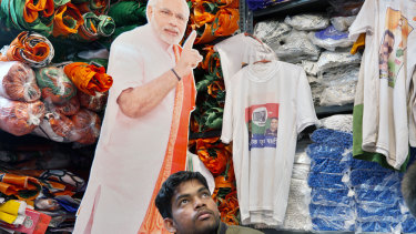 A customer sits in front of a cut-out of India's Prime Minister Narendra Modi in a store selling election merchandise at the Sadar Bazaar market in New Delhi.