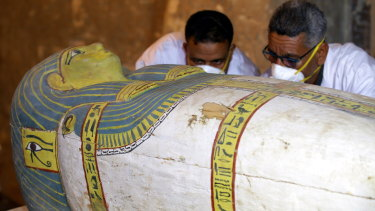 Egyptian archaeologists examine the cover of an intact sarcophagus, inside Tomb TT33 in Luxor, 700 kilometres south of Cairo.