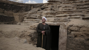 The leader of the excavation stands in front of a newly discovered tomb.