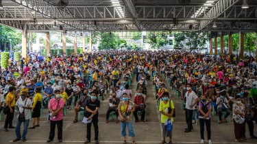 Hundreds of unemployed people wait to apply for government financial aid in Bangkok, Thailand.