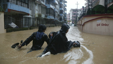 A Nepalese pulls his motorbike and wades past a flooded street in Kathmandu, Nepal, on Friday.