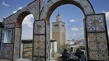 Tunisians take their coffee on a rooftop coffee shop, in the old city of Tunis, Tunisia.
