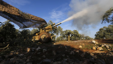 Turkish backed rebel fighters fire a howitzer towards the Syrian government forces' positions near the village of Neirab in Idlib province, Syria, on Thursday.