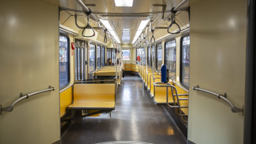 Commuters ride a deserted tram carriage in Milan.