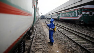 A volunteer sprays disinfectant on a train, in an effort to prevent coronavirus, at the Kamlapur Railway Station in Dhaka, Bangladesh in March.