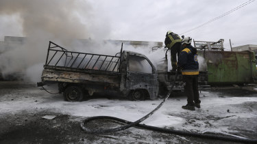 Firefighters hose a truck after a Syrian government air strike in the city of Idlib on Tuesday.