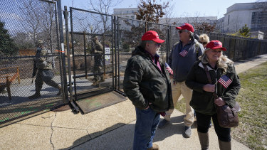 Supporters of former President Donald Trump, John Carson, of California, left, Karyn Carson, right, stand outside of security fencing around the US Capitol.