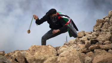 A Palestinian demonstrator uses a sling to hurl stones at Israeli soldiers during a protest against Israeli settlements, in the village of Mughayer, near the West Bank city of Ramallah on Friday.