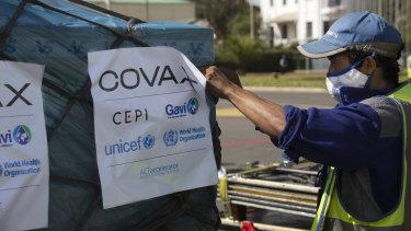 Pekerja bandara menyemprot muatan vaksin Covax COVID-19 setibanya di Antananarivo, Madagaskar.