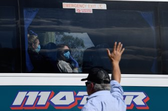 Ruby Princess crew members wave from a bus as it leaves Port Kembla on Tuesday.
