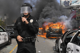 Los Angeles Police Department commander Cory Palka stands among several destroyed police cars.