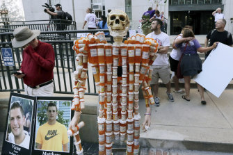 A skeleton made of pill bottles stands with protesters outside a courthouse in Boston, where a judge was hearing arguments against opioid maker Purdue Pharma.