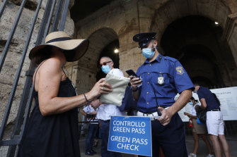 """Tourists have their """"green pass"""" checked by security staff at the entrance of the Colosseum in Rome."""