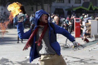 An anti-government protester throws a firebomb at police during a march by students and union members in Santiago, Chile, on Monday.