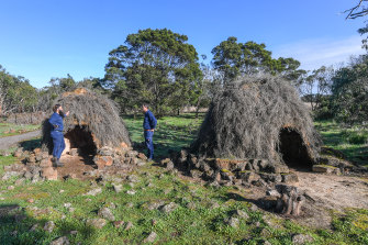 Budj Bim rangers Aaron Morgan and Leigh Boyer stand by replica stone houses in the UNESCO World Heritage-listed Budj Bim cultural landscape.