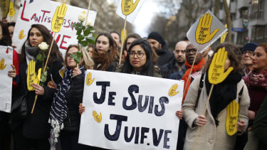 "A woman carries a poster reading ""I am a jew"" as she attends a silent march to honour an 85-year-old woman who escaped the Nazis 76 years ago but was stabbed to death last week in her Paris apartment, apparently because she was Jewish."