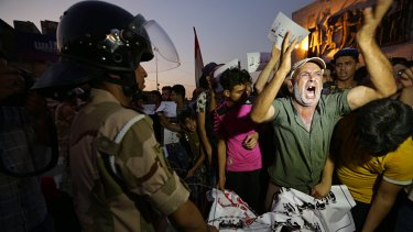 Iraqi protesters chant slogans demanding services and jobs during a demonstration in Tahrir Square, Baghdad, on  Saturday, July 14.