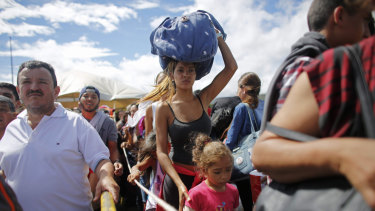 A Venezuelan woman carries a bundle on her head across the border into Colombia.