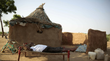A man rests on a bed in front of his hut at a camp for internally displaced people near the town of Abs, Yemen.