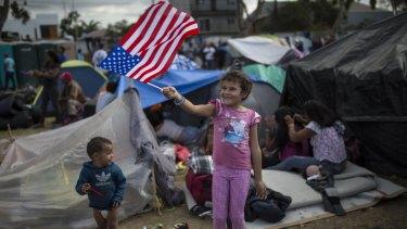 Seven-year-old Honduran migrant Genesis Belen Mejia Flores waves an American flag at US border in Tijuana, Mexico.