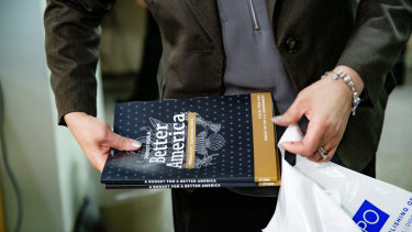 An employee bags purchased copies of US President Donald Trump's 2020 budget request in Washington.