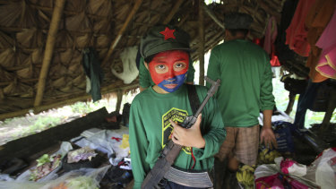 A woman New People's Army guerrilla with her face painted to conceal her identity holds her firearm inside a shelter at a rebel encampment tucked in the harsh wilderness of the Sierra Madre mountains, south-east of Manila, Philippines.