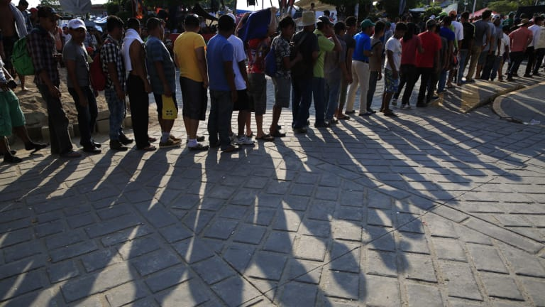 Migrant men wait in line to receive food handouts, in Tapanatepec, Mexico.