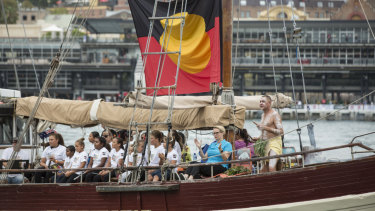 A boat with the Aboriginal flag holds a smoking ceremony in Sydney Cove on Australia Day in 2017.
