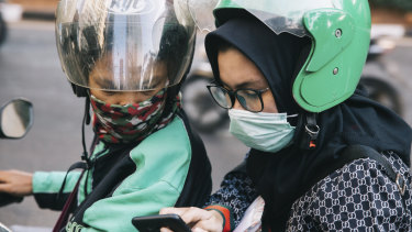 Jakarta commuters wear masks in an effort to filter out the pollution.