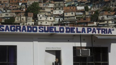 "The Spanish phrase ""Sacred soil of the fatherland"" covers an administrative office at a wholesale food market, near a shantytown in Caracas, Venezuela."