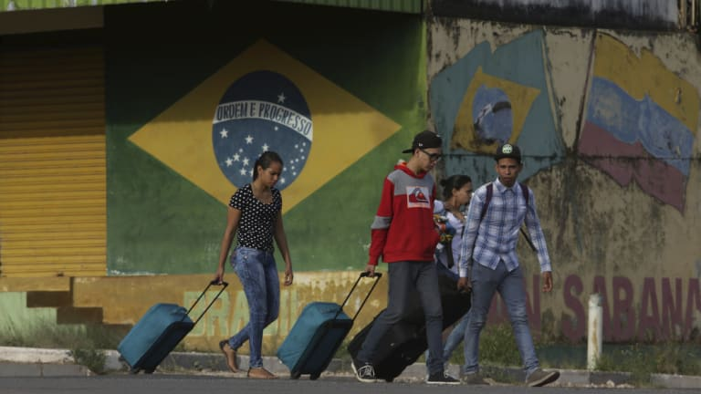 Young Venezuelans pull their luggage after crossing the border to Pacaraima, Roraima state, Brazil.