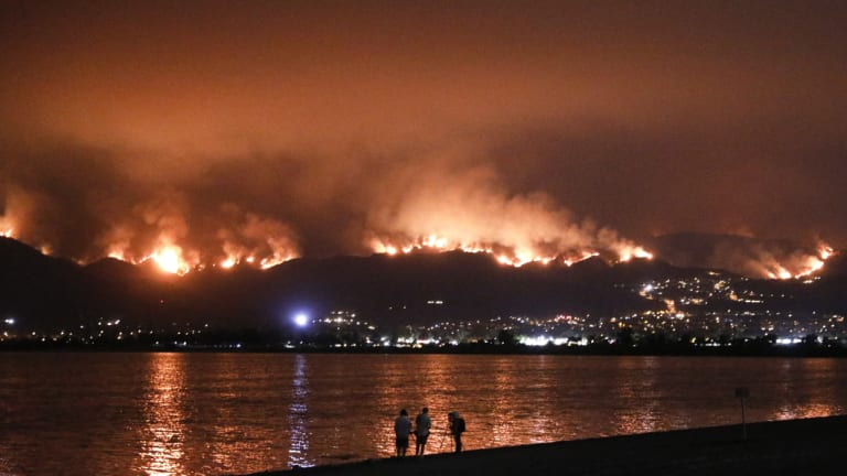 Onlookers are silhouetted against the reflection of a wildfire burning in the Cleveland National Forest in Lake Elsinore, California.