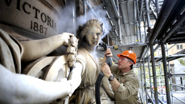 Tyron Timperi applies a steam treatment to restore detail and colour in a marble statue on the GPO building.