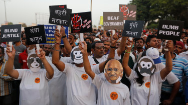 An Indian man wearing a mask of Mahatma Gandhi participates with others in a rally to protest against recent incidents of rape, in Ahmadabad, India, on Wednesday.