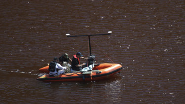 Police use sonar monitoring equipment on a toxic lake in Mitsero, near Cyprus' capital Nicosia, on Saturday. The sonar scans form part of the search for suitcases in which a self-confessed serial killer placed bodies.