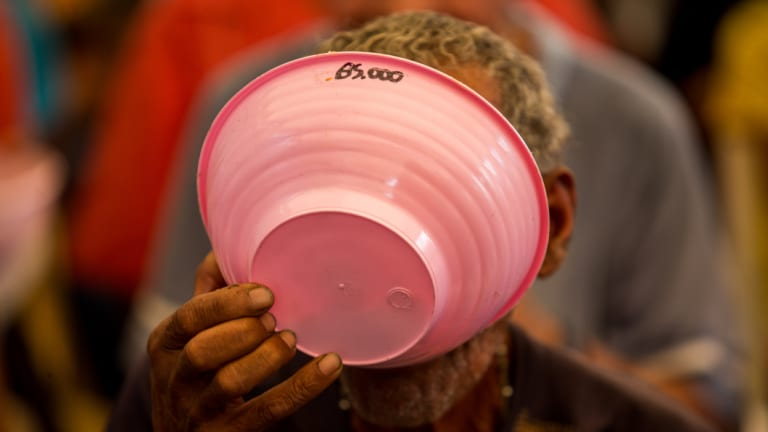 A resident eats free soup at a political rally in Vargas state, Venezuela last week.